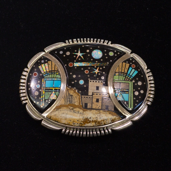A belt buckle featuring the artwork of Calvin Begay